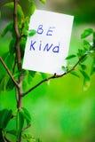 La frase de la motivación sea buena En un fondo verde en una rama es un Libro Blanco con una frase de la motivación Fotografía de archivo