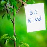 La frase de la motivación sea buena En un fondo verde en una rama es un Libro Blanco con una frase de la motivación Foto de archivo libre de regalías