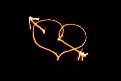 La freccia ardente ha perforato il cuore sul nero Fotografie Stock