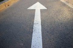 La freccia bianca che indica la direzione immagini stock