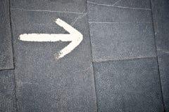 La freccia bianca sul pavimento Fotografie Stock Libere da Diritti