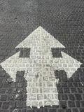 La freccia a tre corsie bianca della direzione canta sui mattoni di pietra Fotografia Stock Libera da Diritti