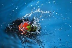 La fresa cae bajo el agua fotos de archivo