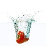 La fresa cae profundamente debajo del agua fotos de archivo