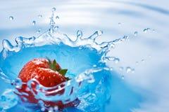 La fresa cae profundamente debajo del agua imagenes de archivo