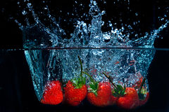La fresa fresca cayó en el agua con el chapoteo en backgro negro Imagenes de archivo