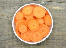 La frescura de cortes corta la zanahoria en el cuenco blanco en de madera Fotos de archivo