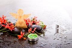 La fresia Laxa del rojo anaranjado florece con las piedras negras del masaje, verde Fotografía de archivo libre de regalías