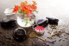 La fresia Laxa del rojo anaranjado florece en el envase de cristal con masaje Foto de archivo libre de regalías