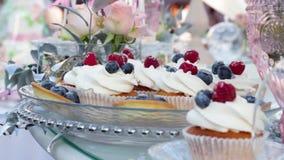 La friandise, table avec des bonbons, les petits gâteaux doux délicieux se trouvent d'une glace sur une table clips vidéos