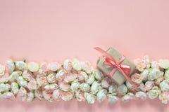 La frontera de pequeñas rosas florece con la caja de regalo en fondo rosado Foto de archivo
