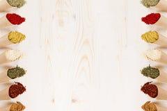 La frontera decorativa del diverso polvo condimenta el primer en las esquinas de papel en el tablero de madera blanco con el espa Imágenes de archivo libres de regalías