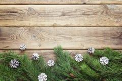 La frontera del abeto ramifica con los conos blancos en los viejos tableros de madera Imagenes de archivo