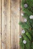 La frontera del abeto ramifica con los conos blancos en los viejos tableros de madera Imagen de archivo libre de regalías