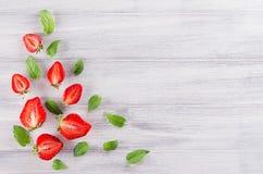 La frontière décorative d'été de la fraise et la menthe poussent des feuilles sur le fond blanc avec l'espace de copie, vue supér Photo stock