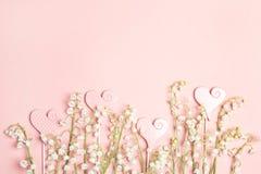 La frontière des fleurs du muguet avec amour entend sur un fond rose photo libre de droits