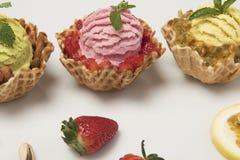 La fruta del pation del pistacho y fresa helado en el fondo blanco con el acompañamiento de las frutas foto de archivo libre de regalías