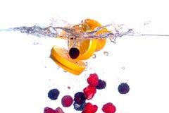 La fruta fresca cae bajo el agua con un chapoteo Fotografía de archivo
