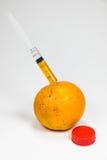La frutta arancio reale è stata succhiata dalla siringa Immagine Stock