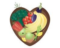 La frutta e le verdure sane del cibo in un cuore hanno modellato la ciotola Immagini Stock