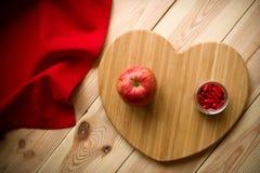 La frutta o le capsule su un cuore ha modellato il tagliere di bambù Fotografia Stock