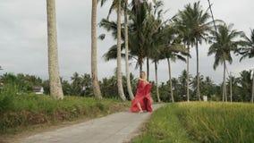 La fucilazione dal fondo, il modello di vista frontale cammina lungo una strada stretta contro il contesto delle palme e del riso archivi video