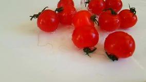 la fucilazione lenta di versamento della vitamina dell'acqua luminosa sana matura dei pomodori, ha bagnato la caduta video d archivio
