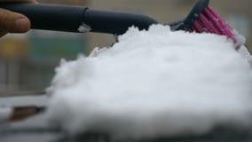 La fucilazione lenta passa la neve di raschio dal parabrezza congelato dell'automobile, fiocchi di neve che circolano sul sole archivi video