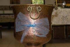 La fuente bautismal adornada del bautizo llenó de agua santa en la iglesia antes de la ceremonia Fotografía de archivo libre de regalías