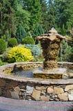 La fuente decorativa original en un jardín botánico Fotos de archivo