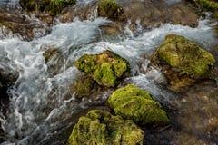 La fuente del río que hace las cascadas sobre rocas cubrió ingenio Imagenes de archivo