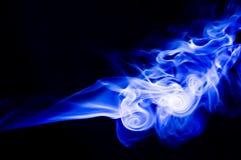 La fumée bleue abstraite tourbillonne au-dessus du fond noir Photographie stock