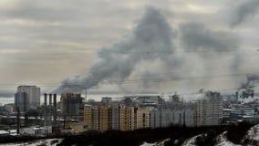 La fumée grise de l'usine métallurgique de tuyaux couvre le buildi de ville Image libre de droits