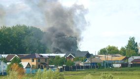 La fumée noire s'est renversée derrière des maisons dans le village clips vidéos