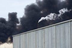 La fumée toxique d'un feu occidental de Footscray le 30 août 2018 peut être beugler vu derrière un entrepôt moderne avec le blanc image libre de droits