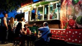 La furgoneta al aire libre acogedora del café, restaurante en la calle, visitantes come, las lámparas encendidas pizzería, un lug metrajes