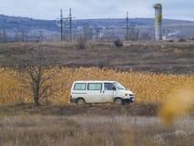 La furgoneta blanca monta en alguna parte abajo del camino Imagen de archivo