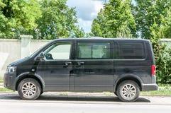 La furgoneta de pasajero negra del transportador de Volkswagen T 5 parqueó en la calle imagenes de archivo