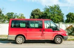 La furgoneta roja usada vieja de Ford Transit del pasajero parqueó en la calle en la ciudad imagenes de archivo