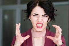 La furia de la rabia de la cara de la emoción estrangula a la mujer que descubre los dientes imagen de archivo libre de regalías