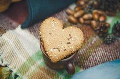 La galleta de la forma de dos corazones está en la tela escocesa de las lanas con las hojas y la bellota otoñales Foco selectivo  Imagenes de archivo