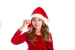 La galleta roja de la campana de la Navidad y Navidad visten a la muchacha del niño Foto de archivo
