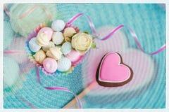 La galleta rosada del pan de jengibre en la forma de un corazón, combinado con los diversos dulces, adornó la oferta fresca subió Imágenes de archivo libres de regalías