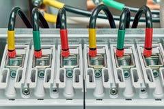 La gama de alambres eléctricos o los cables está conectada con los disyuntores de poder Fotografía de archivo libre de regalías