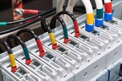 La gama de alambres eléctricos o los cables está conectada con los disyuntores de poder Imagen de archivo libre de regalías