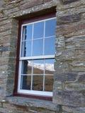 La gama nevada reflejó en la ventana de piedra histórica de la cabaña, Nueva Zelanda imágenes de archivo libres de regalías