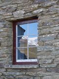 La gama nevada reflejó en la ventana de piedra histórica de la cabaña, Nueva Zelanda fotografía de archivo libre de regalías