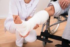 La gamba di medico del paziente femminile della tenuta immagine stock libera da diritti