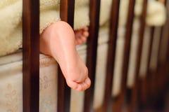 La gamba/tallone di un bambino addormentato ha attaccato fuori da una coperta da una greppia del bambino immagine stock