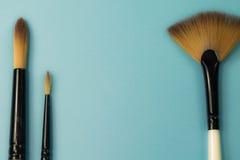 La gamma artistica di concetto di fan piano dei pennelli rotondo con i capelli naturali del nero rizza sul fondo blu del turchese Fotografie Stock